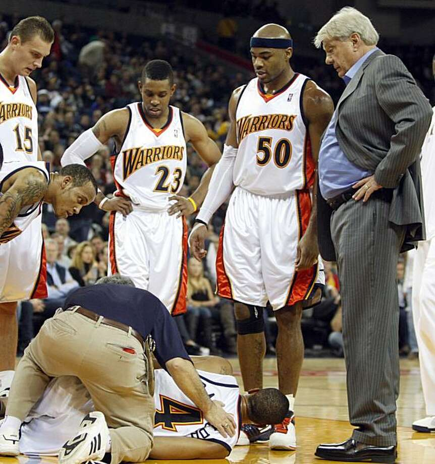 Golden State Warriors coach Don Nelson, right, with Warriors, from left, Andris Biedrins, C.J. Watson (23) and Corey Maggette (50), check on the condition of Anthony Randolph (4) after Randolph injured his ankle during the first half of an NBA basketballgame against the Sacramento Kings, on Friday, Jan. 8, 2010, in Oakland, Calif. Photo: Ben Margot, AP