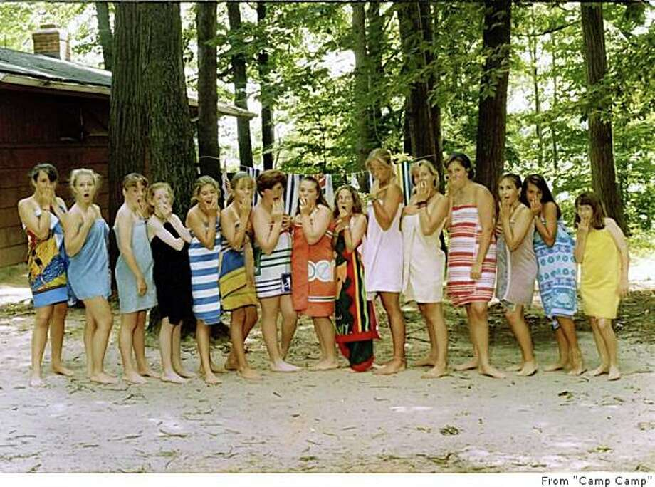 "Following the instructions of their camp counselors, the girls at Camp Echo, in Fremont, Michigan circa 1991, take off their swinsuit straps and hide them under towels. Printed in ""Camp Camp: Where 'Fantasy Island' Meets 'Lord of the Flies'"" Photo: From ""Camp Camp"", Courtesy Of Claire Zulkey"