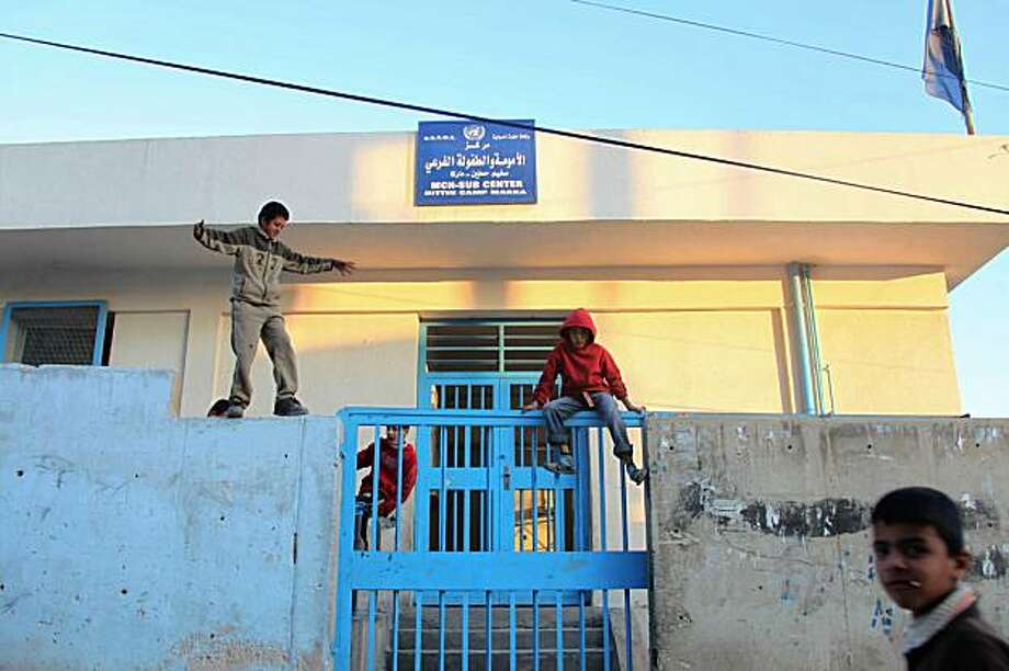 Jordanian boys play on January 5, 2010 outside the gate of an UNRWA clinic, where Jordanian Al-Qaeda triple agent Humam Khalil Abu Mulal al-Balawi used to work as a doctor, in a refugee camp in the impoverished Amman satellite city of Zarqa, east of the Jordanian capital. A suicide bomber who killed eight people at a CIA base in Afghanistan was an Al-Qaeda triple agent who duped Western intelligence services for months before turning on his handlers, jihadist websites boasted, adding that he was born near Zarqa, hometown of Al-Qaeda in Iraq leader Abu Musab Al-Zarqawi, who became infamous for a series of videotaped beheadings of Western hostages before his death in a US air strike in June 2006. Jordanian Islamist sources said that Balawi, 36, was a doctor by profession and a married father of two. AFP PHOTO/KHALIL MAZRAAWI (Photo credit should read KHALIL MAZRAAWI/AFP/Getty Images) Photo: Khalil Mazraawi, AFP/Getty Images