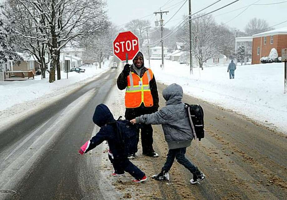 Blackhawk Elementary School crossing guard Kenneth Hines, of Freeport, Ill., center, stops traffic as Dereisha Sims, 7, of Freeport, Ill., left, and Rebecca Pehl, 8, of Freeport, Ill. leave school Thursday, Jan. 7, 2010, in Freeport, Ill. Area schools had an early dismissal due to bad weather. (AP Photo/The Journal-Standard, Stefanie Weiss) MANDATORY CREDIT Photo: Stefanie Weiss, AP