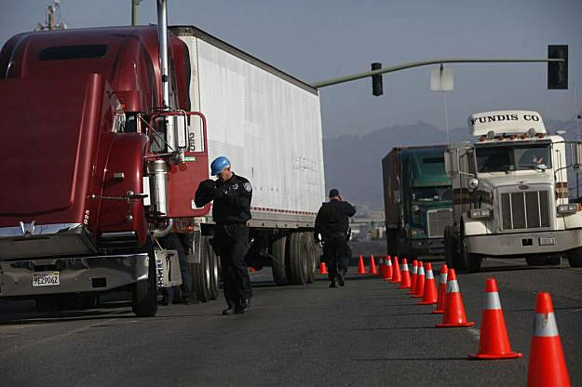 Joined by other police from around Alameda County, San Leandro Police Officer Jeff Bouillerce inspects trucks near the port of Oakland for safety violations on Monday, Dec. 21, 2009 in San Francisco, Calf. Regular inspections conducted by participating law enforcement agencies from Commercial Officers of Southern Alameda County (COSAC) were moved up by two days in order to create a police presence in the event of a trucker walk out.