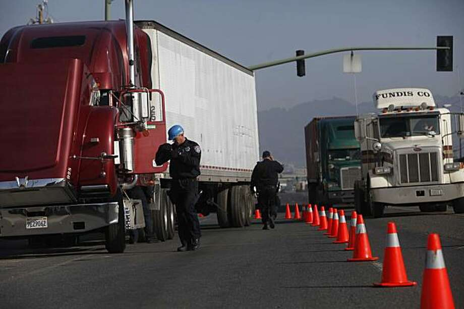 Joined by other police from around Alameda County, San Leandro Police Officer Jeff Bouillerce inspects trucks near the port of Oakland for safety violations on Monday, Dec. 21, 2009 in San Francisco, Calf. Regular inspections conducted by participating law enforcement agencies  from Commercial Officers of Southern Alameda County (COSAC) were moved up by two days in order to create a police presence in the event of a trucker walk out. Photo: Mike Kepka, The Chronicle