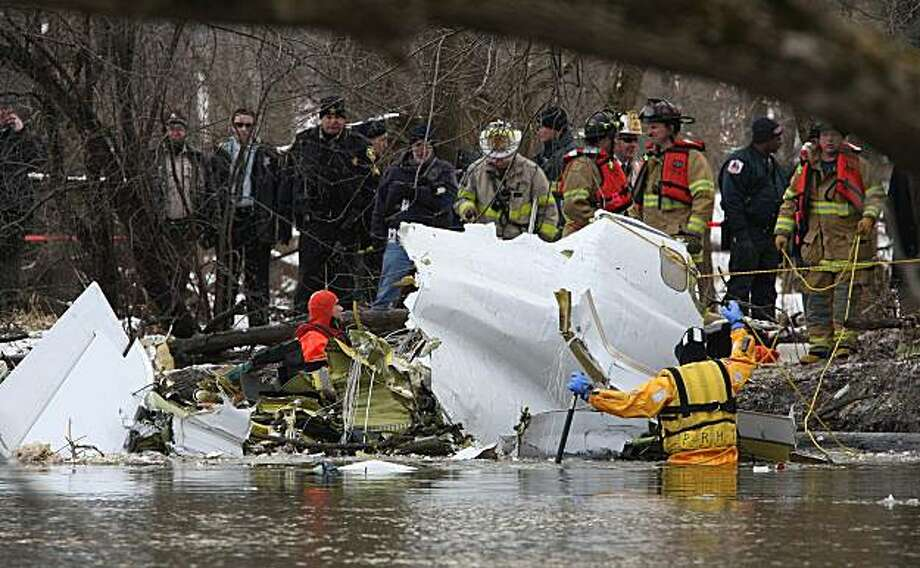 Authorities comb the wreckage of a small plane that crashed Tuesday, Jan. 5, 2010, in Glenview, Ill. Authorities say a Royal Air cargo jet had been cleared for landing before it crashed in a forest preserve near Chicago Executive Airport in nearby Wheeling, Ill. It was not known immediately know how many people were aboard and if there were injuries. (AP Photo/Mike Anzaldi) Photo: Mike Anzaldi, AP