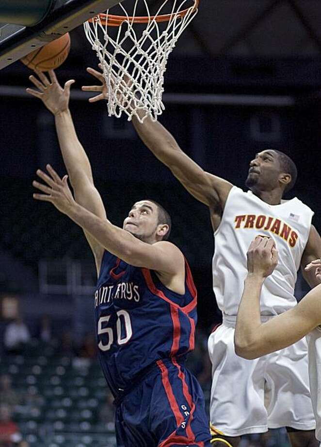 Saint Mary's center Omar Samhan (50) puts up a shot while being defended by Southern California forward Marcus Johnson, right, in the first half of an NCAA college basketball game Wednesday Dec. 23, 2009, at the Diamond Head Classic in Honolulu. (AP Photo/Eugene Tanner) Photo: Eugene Tanner, AP
