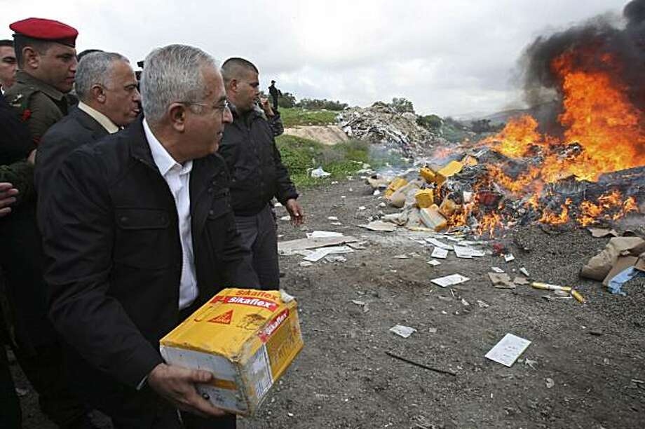 Palestinian Prime Minister Salam Fayyad, throws a package into a fire set to burn products from Jewish settlements,  in the west Bank of Salfit Tuesday, Jan 5, 2010.  The Palestinians have launched a boycott of Israeli products made in Jewish settlements in the West Bank.(AP Photo/Nasser Ishtayeh) Photo: Nasser Ishtayeh, AP