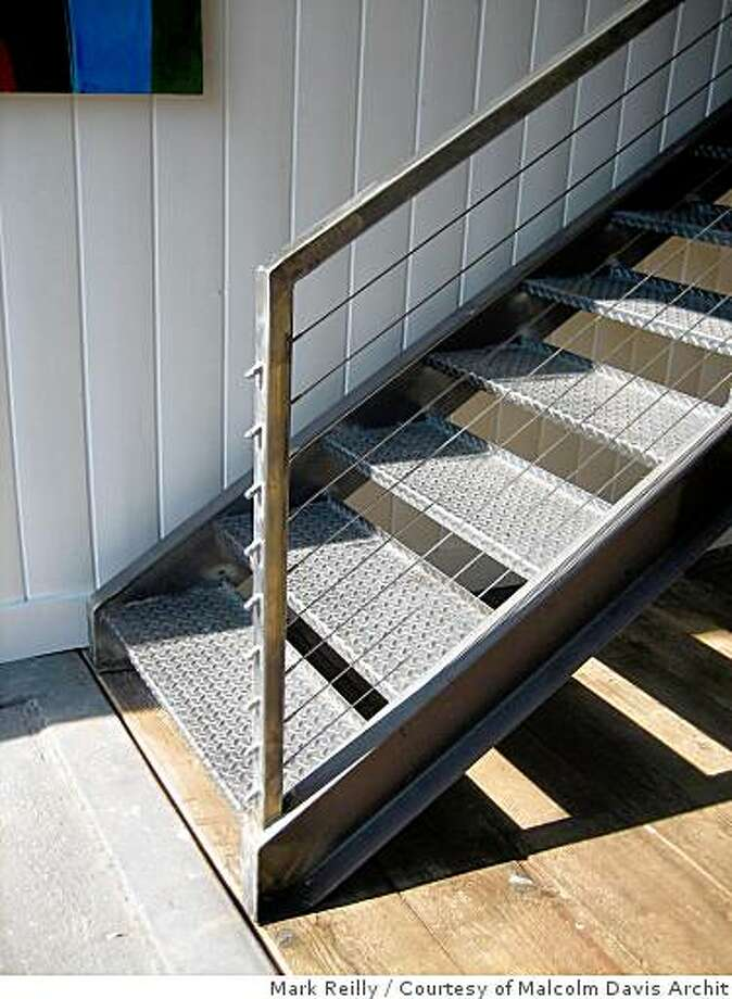 Custom steel stairs with cable railings insode The former carriagehouse in San Francisco's Missiopn district after architect Malcolm Davis completed spaces within it for several businesses, including a rental apartment, a commercial kitchen for caterers, a casual cafe called Stable and his own office, Malcolm Davis Architecture in the mezzanine and floor above. The building has a adjacent vacant lot that is used as a ciommunal courtyard. Photo: Courtesy Of Malcolm Davis Archit, Mark Reilly