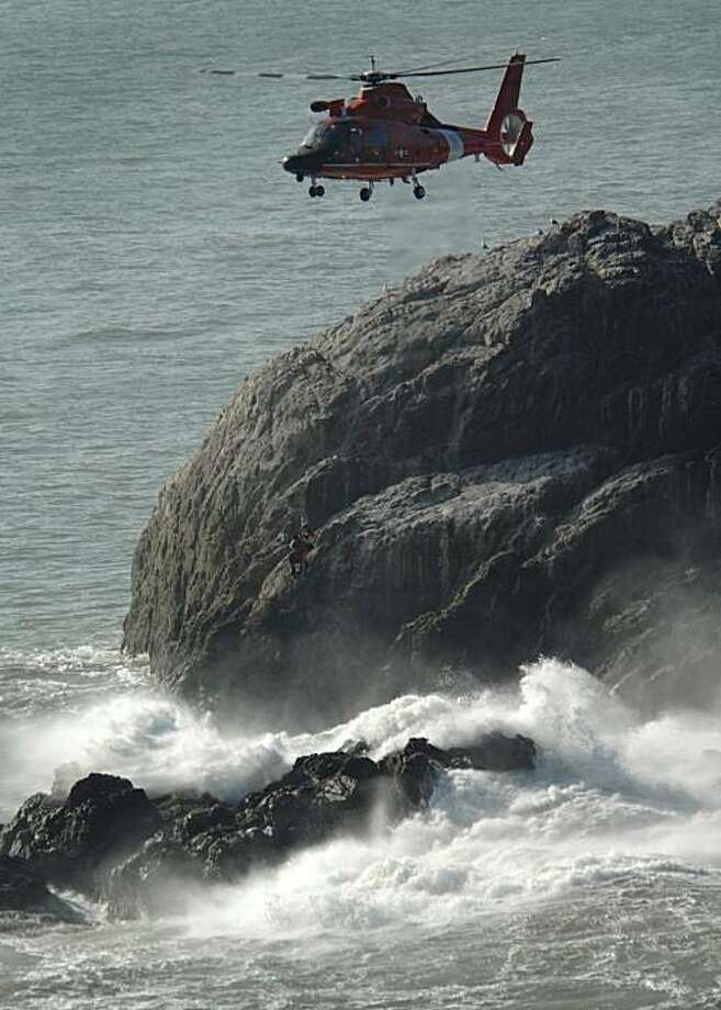 A Coast Guard helicopter rescues a surfer who was stranded on a rock near Lands End in San Francisco, Calif., on Monday, Jan. 4, 2010. The unidentified surfer was transferred safely back to the shore around 12:15 p.m.  A Coast Guard helicopter rescues a surfer who was stranded on a rock near Lands End in San Francisco, Calif., on Monday, Jan. 4, 2010. The unidentified surfer was transferred safely back to the shore around 12:15 p.m. Photo: Gary Jung, Special To The Chronicle
