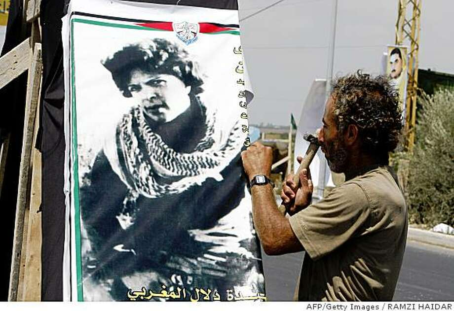 CORRECTING CITYA Lebanese man hangs a poster of Palestinian Fatah member Dalal al-Mughrabi in Naqura in southern Lebanon on July 15, 2008. Mughrabi led a commando attack on an Israeli bus in April 1978. Her body is due to be returned tomorrow during a prisoner swap between Lebanon's Hezbollah and Israel. Five Lebanese prisoners, including Samir Kantar, the perpetrator of a brutal 1979 triple murder, will be swapped for two soldiers captured by Hezbollah in a deadly 2006 raid that sparked a vicious 34-day war. Israel will also hand over the remains of 200 Lebanese and Palestinians. AFP PHOTO/RAMZI HAIDAR (Photo credit should read RAMZI HAIDAR/AFP/Getty Images) Photo: RAMZI HAIDAR, AFP/Getty Images