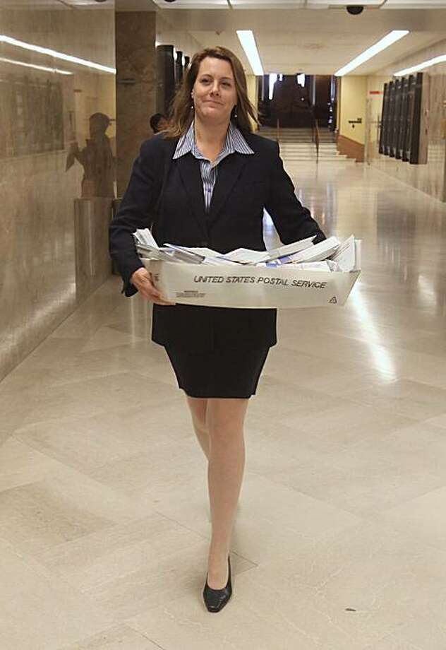 Assemblywoman Alyson Huber, D-Lodi,  carries a tray containing more than 2,000 postcards from constituents,  who are opposed to the construction of a peripheral canal, to the Governor's office in Sacramento, Calif., Monday, Nov. 9, 2009. The Legislature approved a package of water measures last week that critics say will make it easier to build a canal that diverts water from Northern California around the Sacramento-San Joaquin delta to Southern California.(AP Photo/Rich Pedroncelli) Photo: Rich Pedroncelli, AP