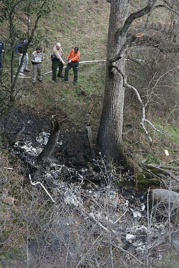 Law enforcement personnel survey the site where a California Fish and Game helicopter crashed, caught fire and burned after apparently clipping a power line near Road 235 in Madera County on Tuesday. Photo: Mark Crosse, AP