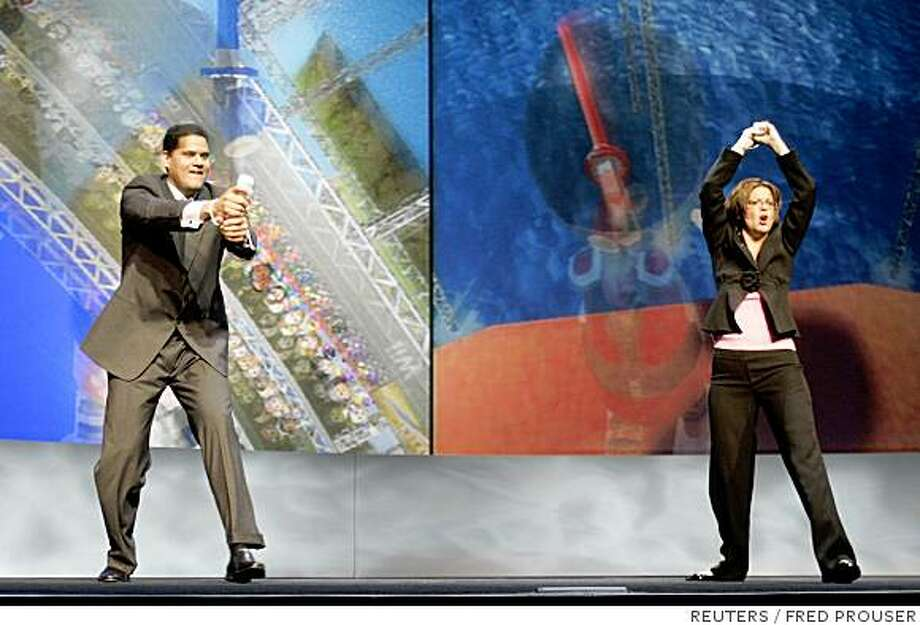Reggie Fils-Aime (L), president and chief operating officer of Nintendo America Inc., and Cammie Dunaway, executive vice president of sales and marketing, demonstrate the 'Wii Sports Resort' at the Nintendo E3 media briefing in Hollywood, California July 15, 2008.  REUTERS/Fred Prouser (UNITED STATES) Photo: FRED PROUSER, REUTERS