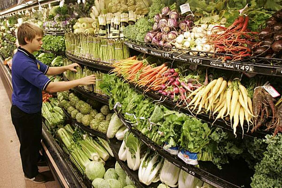 Sean Meagher works on a vegetable display in the produce department of a Kroger store, Wednesday, July 16, 2008, in Cincinnati. Food prices showed a big increase nationally in June, rising 0.7 percent. Vegetable prices shot up by 6.1 percent nationally, the biggest increase in nearly three years. (AP Photo/Al Behrman)