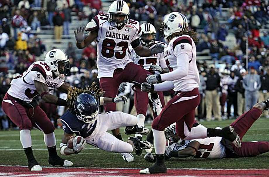 Connecticut's Andre Dixon (2) slips through five South Carolina defenders for a touchdown in the fourth quarter of the Papajohns.com Bowl. Connecticut defeated South Carolina, 20-7, at Legion Field in Birmingham, Alabama, Saturday, January 2, 2010. (John Woike/Hartford Courant/MCT) Photo: John Woike, MCT