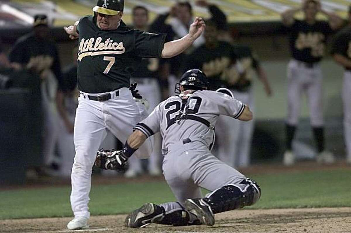 ATHLETICS21-C-13OCT01-SP-CG --- Oakland Athletics' designated hitter, Jeremy Giambi, was called out on this controversial play that would've scored the tying run at home plate in the bottom of the seventh inning against the New York Yankees at Network Associates' Coliseum on Saturday, October 13, 2001. New York catcher is Jorge Posada. (Photo by Carlos Avila Gonzalez/The San Francisco Chronicle)