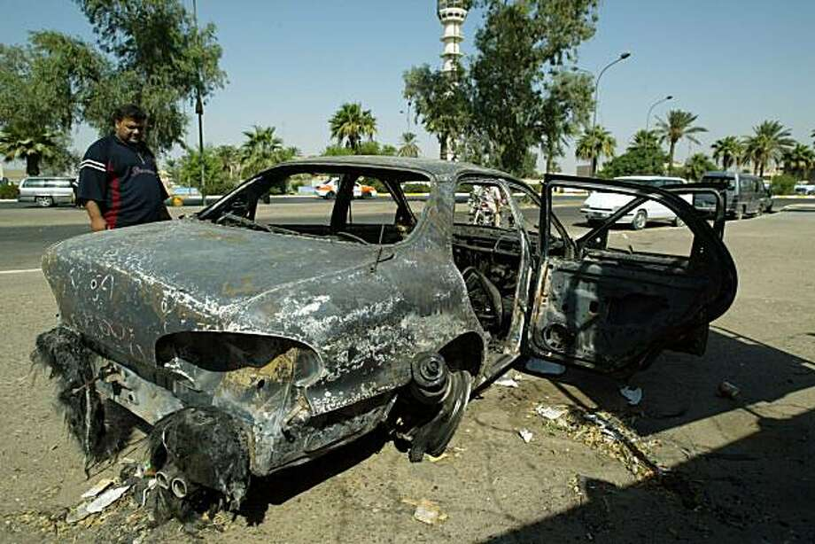 (FILES) An Iraqi looks at a burnt car on September 24, 2007, at the site where Blackwater guards, who were escorting US embassy officials, opened fire in the Baghdad neighborhood of Yarmukh on September 16. On December 31, 2009, US District Judge Ricardo Urbina dismissed all charges against five Blackwater guards over the killing of 17 Iraqis in the 2007 shootout. Five guards from the US Security firm were accused of firing on a crowd at an intersection in Baghdad. Urbina said the US Justice Department had used evidence prosecutors were not supposed to have. The five had pleaded not guilty to manslaughter. A sixth guard admitted to killing at least one Iraqi.       FILES/AFP PHOTO/ALI YUSSEF (Photo credit should read ALI YUSSEF/AFP/Getty Images) Photo: Ali Yussef, AFP/Getty Images