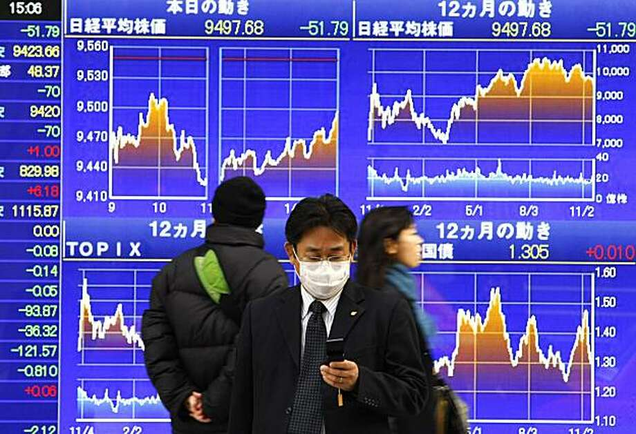 FILE - In this Nov. 20, 2009 file photo, a man checks Japan's Nikkei stock index on the indication board while a man with a mask checks his mobile phone in front of a securities firm in Tokyo. Trounced in last year's financial crisis, Asian stocks helped lead 2009's global rally as unprecedented government stimulus measures and economic recovery lured investors back to the region's markets en masse. (AP Photo/Shizuo Kambayashi, File) Photo: Shizuo Kambayashi, AP