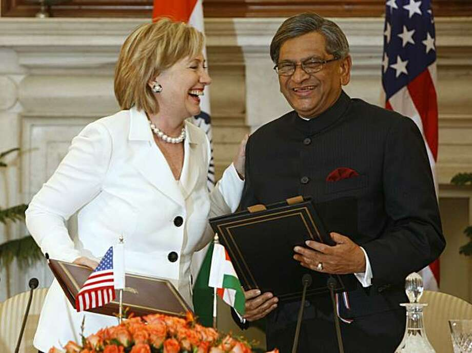 U.S. Secretary of State Hillary Rodham Clinton, left, shares a light moment with Indian Foreign Minister SM Krishna, as they exchange documents after signing an agreement on an endowment fund for science and technology in New Delhi, India, Monday, July 20, 2009. Clinton touted prospects for strengthening U.S.-India relations, despite sharp differences on carbon emissions, as they readied a pact giving U.S. companies more access to India's expanding markets. (AP Photo/Mustafa Quraishi) Photo: Mustafa Quraishi, AP