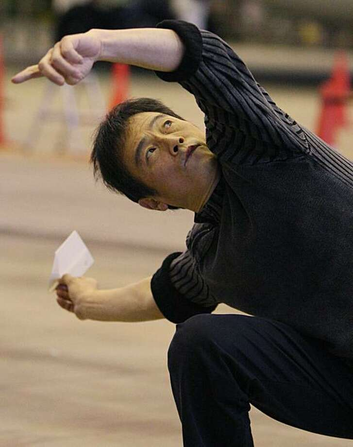 Japanese paper airplane virtuoso Takuo Toda prepares to release a 10-centimeter-long craft  during his paper airplane fly-off in attempt to break his own record of 27.9 seconds set earlier this year,  at a Japan Airlines hangar near Haneda Airport in Tokyo, Japan,  Sunday, Dec. 27, 2009.  In the world of competitive paper airplane throwing, a 20-second flight is exceptional, 25 or better is world class.   Thirty is the stuff that dreams are made of.  Toda has ever come close to breaking the 30-second barrier. On Sunday, he set a world record for a hand-launched plane made with only paper, but fell just short of the 30-second mark. (AP Photo/Koji Sasahara) Photo: Koji Sasahara, AP