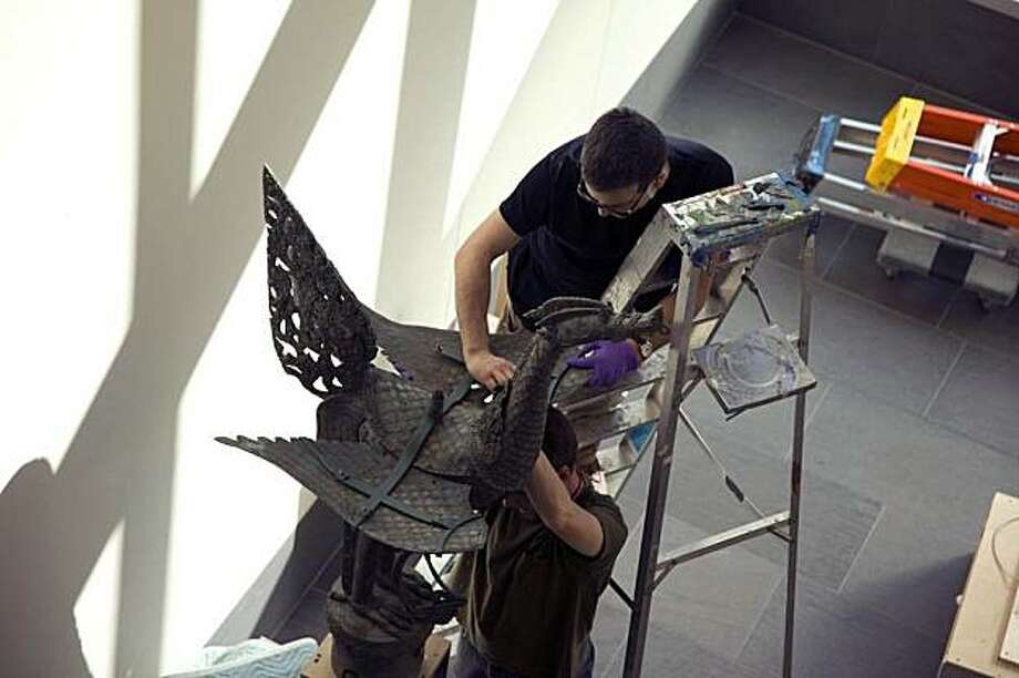 At the Asian Art Museum, mount maker Vince Avalos and assistant secure an antique cast-brass Thai street lamp (a mythical bird) against potential earthquake damage, placing it on a vertical steel armature with a heavily weighted base; a custom-fabricated brace keeps the bird's wings spread. Photo: Kaz Tsuruta, Asian Art Museum, S.F.
