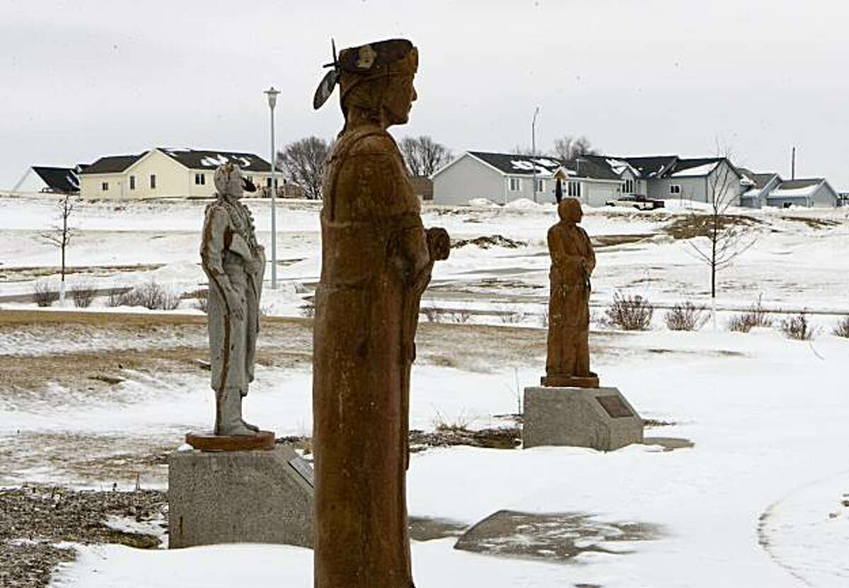 This Jan. 30, 2009 photo shows statues depicting the various clans within the Winnebago tribe, overlooking a housing development north of Winnebago, Neb., which was built on land purchased by the tribe. Native American tribes tired of waiting for the U.S. government to honor centuries-old treaties are buying back land where their ancestors lived and putting it in federal trust. (AP Photo/Nati Harnik)