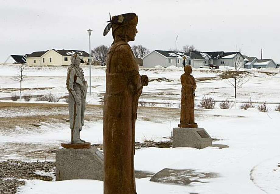 This Jan. 30, 2009 photo shows statues depicting the various clans within the Winnebago tribe, overlooking a housing development north of Winnebago, Neb., which was built on land purchased by the tribe. Native American tribes tired of waiting for the U.S. government to honor centuries-old treaties are buying back land where their ancestors lived and putting it in federal trust. (AP Photo/Nati Harnik) Photo: Nati Harnik, AP