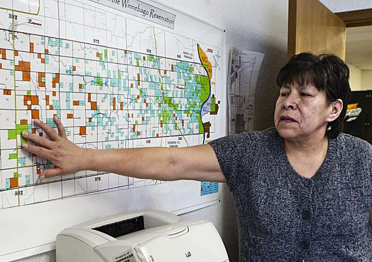 This photo from Jan. 30, 2009, shows Faye Houghton, who is in charge of the Winnebago tribe's land management, pointing on a map hanging in her Winnebago, Neb., office, to a green color-coded 384 acre parcel of land which was bought in 2004 from a private land owner. Native American tribes tired of waiting for the U.S. government to honor centuries-old treaties are buying back land where their ancestors lived and putting it in federal trust. (AP Photo/Nati Harnik)
