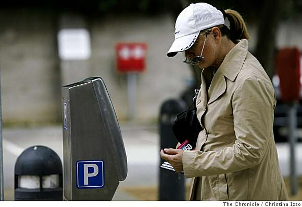 Linda DeHennis, a San Francisco local, takes a minute to read the instructions on the new parking meter in a city-owned parking lot on Wednesday, July 16, 2008, San Francisco, Calif. San Francisco is testing a new parking program at a city-owned lot on California Street in which individual meters have been replaced with pay stations on Wednesday, July 16,2008, San Francisco, Calif. Photo by Christina Izzo / The Chronicle