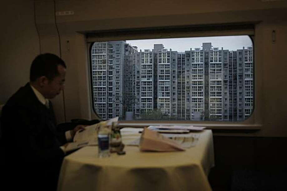 In this photo taken Oct. 29, 2008, a man commutes on the fast train from Tianjing to Beijing, China. In the sprawling megacities of Beijing, Shanghai and Chongqing, where populations exceed 10 million people, extreme urban density means that the number of people living within a few blocks equals those in a whole mid-size U.S. city. China's urban population soared to 607 million last year out of a population of 1.3 billion. Three decades ago nearly 80 percent lived in the countryside, but urbanization continues unabated as job-seeking rural migrants flood into cities. The scale and pace continues to soar, and by current trends, the urban population will hit one billion by 2030. (AP Photo/Elizabeth Dalziel) Photo: Elizabeth Dalziel, AP