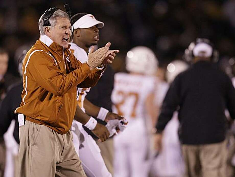 "FILE - In this Oct. 24, 2009, file photo, Texas head coach Mack Brown cheers from the sidelines during the first quarter of an NCAA college football game against Missouri in Columbia, Mo. An Associated Press review of admissions data submitted to the NCAA by most of the 120 schools in college football's top tier shows that athletes enjoy strikingly better odds of having admission requirements bent on their behalf.  Texas was one of seven schools that reported no use of special admissions, instead describing ""holistic"" standards that consider each applicant individually rather than relying on minimum test scores and grade-point averages. But the school also acknowledged in its NCAA report that athletic recruits overall are less prepared. (AP Photo/Jeff Roberson, File) Photo: Jeff Roberson, AP"