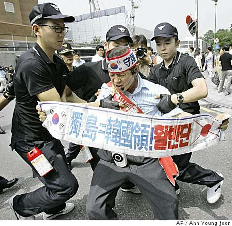 "A South Korea protester struggles with riot policemen during a rally against Japanese description of  Dokdo islets, known as ""Takeshima"" in Japan, as its territory in its educational document, in front of the Japanese Embassy in Seoul, South Korea, Monday, July 14, 2008. The letters on the banner read: "" Dokdo is Territoy of South Korea."" (AP Photo/Ahn Young-joon) Photo: Ahn Young-joon, AP"
