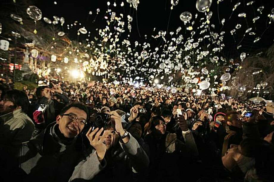 Crowds celebrate as balloons are released to mark the New Year at the Zojoji Temple, in Tokyo, seconds after midnight Friday, Jan. 1, 2010. (AP Photo/Greg Baker) Photo: Greg Baker, AP