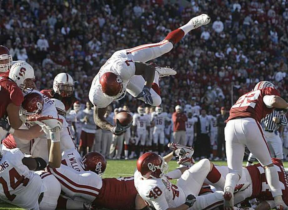 Oklahoma running back DeMarco Murray (7) leaps over the line to score a touchdown during the third quarter of the Sun Bowl NCAA football game against Stanford in El Paso, Texas, Thursday, Dec. 31, 2009. Oklahoma won 31-27. (AP Photo/LM Otero) Photo: LM Otero, AP