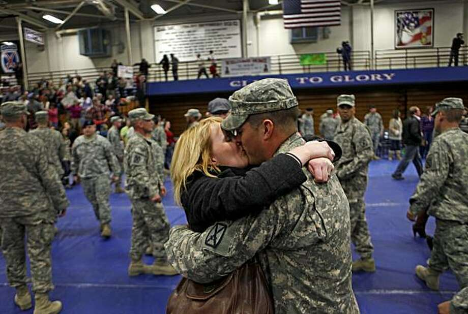 Natalie Pickett, 23, left, kisses her husband, Sgt. Paul Pickett, 23, both of Minden, La., as his unit, the U.S. Army's Apache Company, 2nd Battalion 87th Infantry Regiment, returns from a year-long deployment in Afghanistan in Fort Drum., N.Y. Thursday Dec. 31, 2009. (AP Photo/David Goldman) Photo: David Goldman, AP