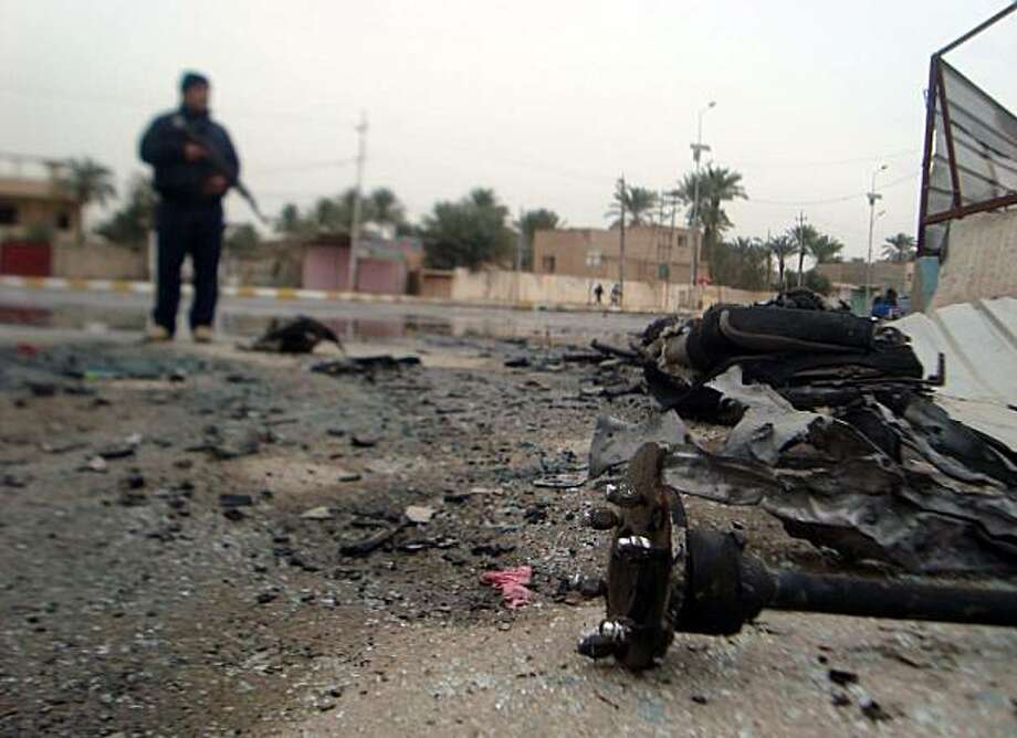 Debris litters the road following two bombings in the western city of Ramadi, 100 kms (60 miles) from Baghdad on December 30, 2009. Blasts in central and western Iraq killed 30 people and wounded the Anbar provincial governor, the latest in a series of attacks against government targets in recent months. AFP PHOTO / AZHAR SHALLAL (Photo credit should read AZHAR SHALLAL/AFP/Getty Images) Photo: Azhar Shallal, AFP/Getty Images