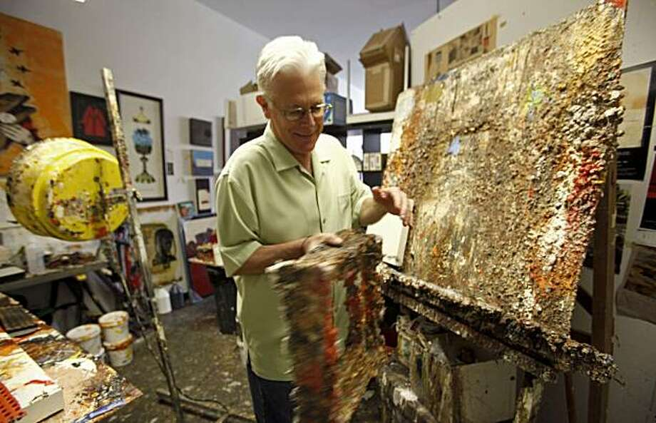 This photo taken Oct. 29, 2009 shows Father Bill Moore touching one of his pieces of art , in his studio at the Pomona Arts Colony in Pomona, Calif., is head of the Ministry of the Arts for the West Coast branch of his religious order, the Sacred Hearts of Jesus and Mary. His job is to serve God by painting whatever comes to mind. (AP Photo/Damian Dovarganes) Photo: Damian Dovarganes, AP