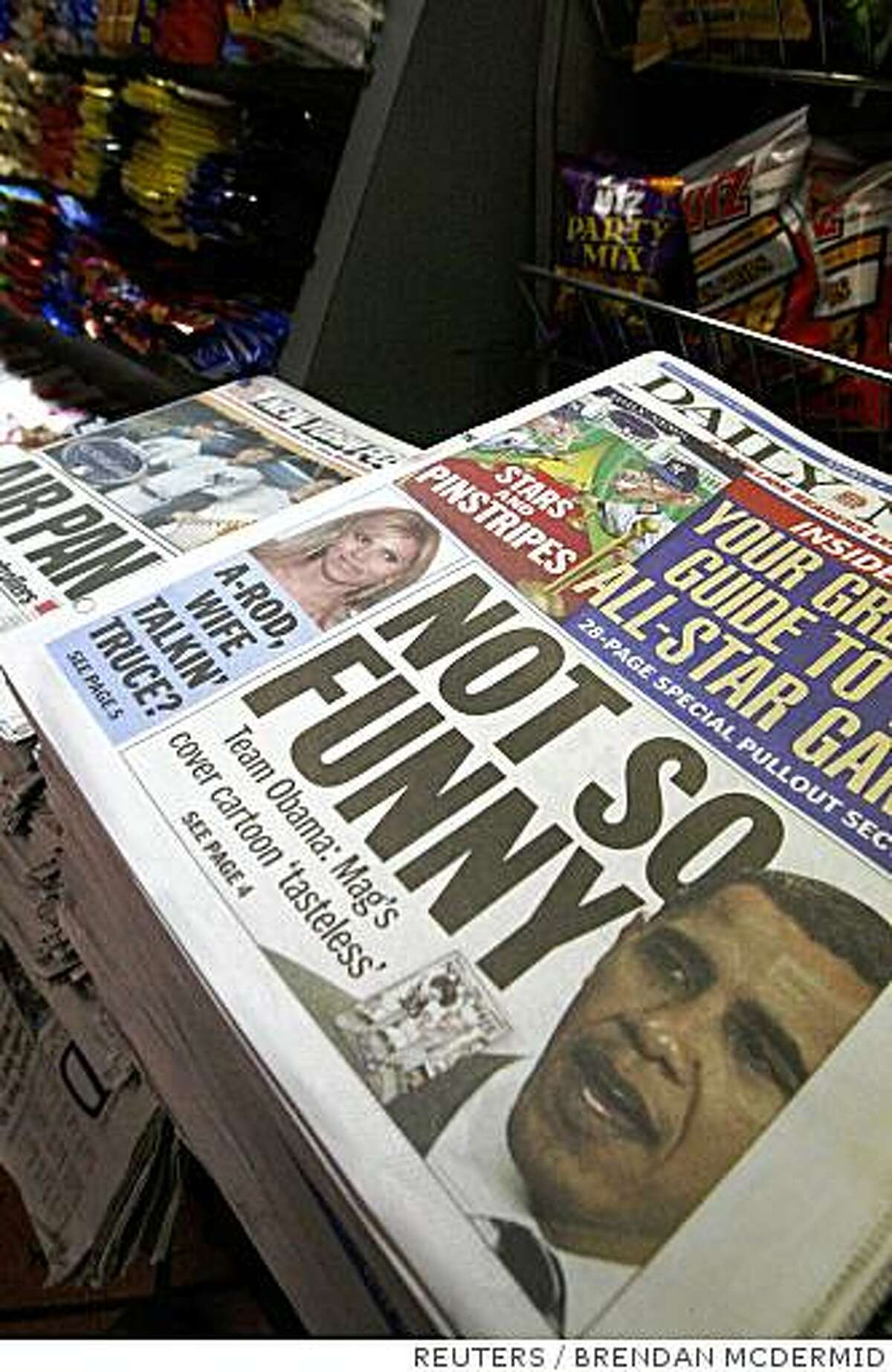 """A copy of the New York Daily News displays a story about the """"The New Yorker"""" magazine cover which featured an illustration of Barack Obama with a turban and robe, at New York's Grand Central Station, July 14, 2008. The magazine pokes fun at smears directed at Barack Obama, but the Democratic presidential candidate isn't laughing. The cover portrays the Illinois senator in a turban and robe bumping fists with wife Michelle, who sports an Afro, a rifle and military garb. In the background, an American flag burns in the fireplace. REUTERS/Brendan McDermid (UNITED STATES)"""