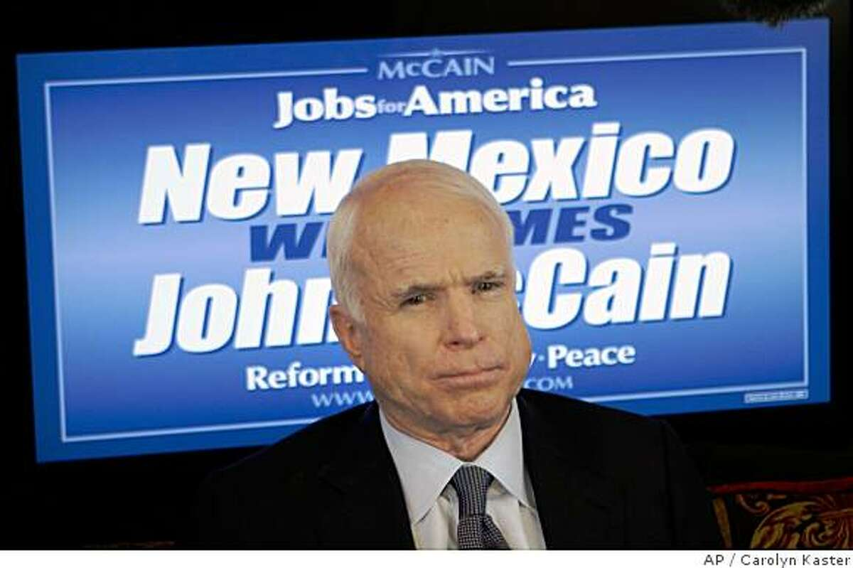 Republican presidential candidate Sen. John McCain, R-Ariz., listens to a reporter's question while talking with reporters aboard his campaign bus as he drives to the airport in Albuquerque, N.M., Tuesday, July 15, 2008. (AP Photo/Carolyn Kaster)