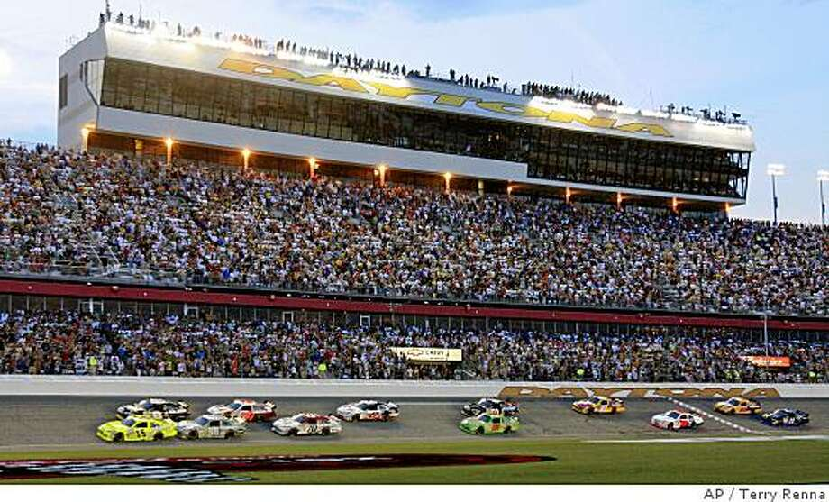 NASCAR driver Paul Menard (15) leads the field through the tri-oval to start the Coke Zero 400 auto race Saturday night July 5, 2008 at the Daytona International Speedway in Daytona Beach, Fla. (AP Photo/Terry Renna) Photo: Terry Renna, AP