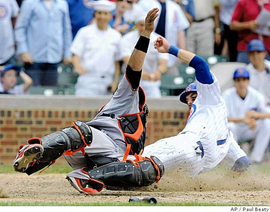 Chicago Cubs' Mark DeRosa scores the winning run while San Francisco Giants catcher Bengie Molina tries to apply the tag in the 11th inning of a baseball game in Chicago, Saturday, July 12, 2008. Chicago won 8-7. Associated Press photo by Paul Beaty Photo: Paul Beaty, AP