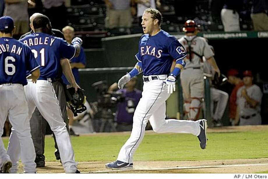 Texas Rangers' Josh Hamilton heads to home plate and waiting teammates after hitting a the game-winning, two-run home run in the ninth inning of the baseball game against the Los Angeles Angels in Arlington, Texas, Wednesday, July 9, 2008. Photo: LM Otero, AP