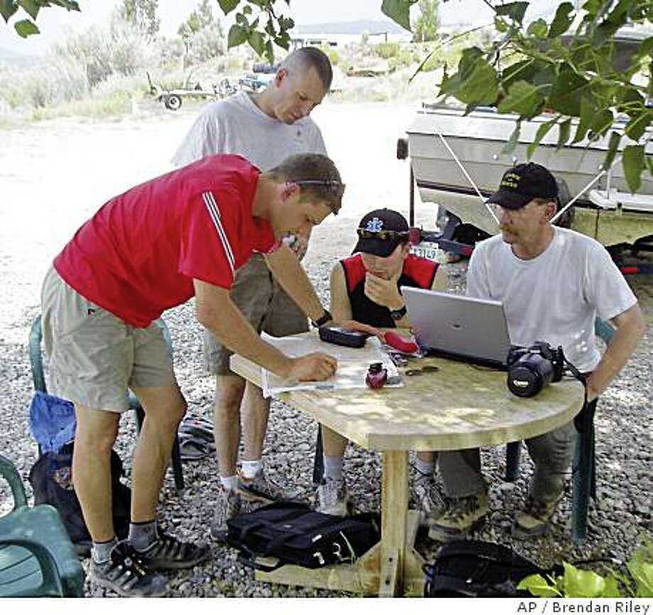 From left to right, team leader Simon Donato, Greg Francek, Tyler LeBlanc and Keith Szlater are seen at the search base camp looking at a map of the search area for multimillionaire adventurer Steve Fossett Sunday, July 13, 2008, in Bridgeport, Calif. The search for Fossett, who vanished in September 2007 after taking off by plane from a remote Nevada ranch, is set to resume Monday, July 14, 2008, in rugged mountains on the California-Nevada line where he may have crashed. (AP Photo/Brendan Riley) Photo: Brendan Riley, AP