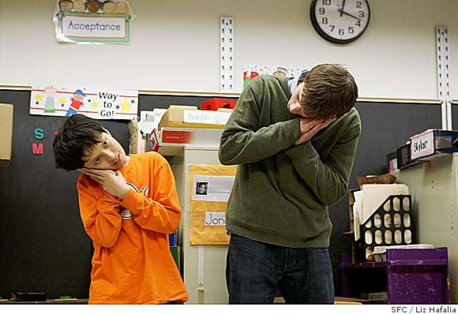 Jonah Kasoff, an 11 year old autistic child, taking a special day class at Yick Wo elementary school where he copies the actions of his teachers leading the class through music in San Francisco, CA, on Monday, Feb.25 2008.  Joel Wilson (right), is a para professional with the autism team.  There is a rise in autistic children in California schools. Photo by Liz Hafalia/San Francisco Chronicle Photo: Liz Hafalia, SFC