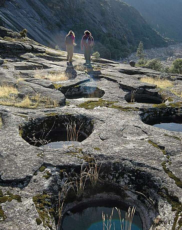 An up-close view of a few of salt basins created by the Miwok Indian tribe in the Sierra to make salt for trade. The people in the photo are unidentified. Photo: US Geological Survey