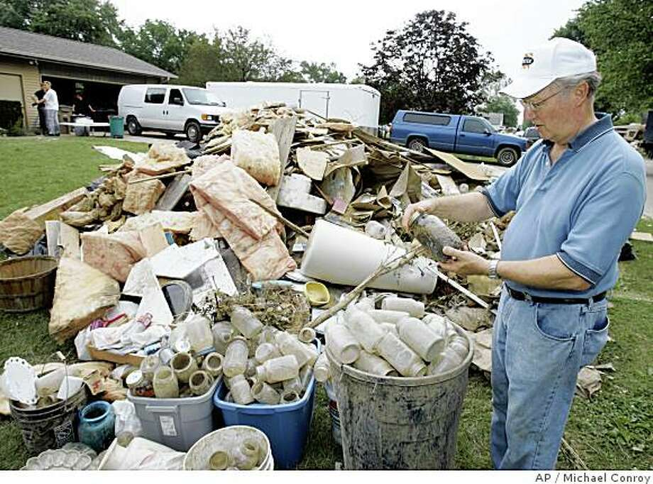 David Spicer looks over items in a trash pile outside his home in Columbus, Ind., Friday, June 13, 2008. Spicer, who does not have flood insurance, has gutted his one-story home after a nearby creek flooded last weekend and damaged his home. Only 1 percent of all Indiana homeowners have flood insurance. (AP Photo/Michael Conroy) Photo: Michael Conroy, AP