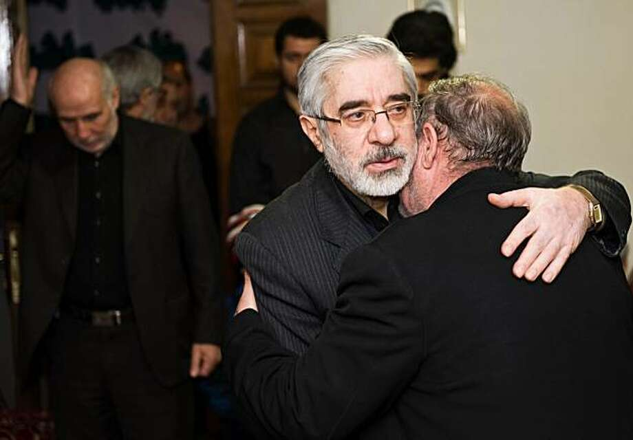 "Iranian opposition leader Mir Hossein Mousavi (C) receives condolences for the death of his nephew Seyed Ali Habibi-Mousavi, on December 28, 2009 in Tehran. The 35-year-old nephew of Mir Hossein Mousavi was shot dead in Tehran during protests on December 27 which turned into the bloodiest showdown between opposition protesters and security forces in months. Iranian police said on December 29 that ""terrorists"" killed the nephew of opposition leader Mir Hossein Mousavi in an incident unrelated to anti-government riots at the weekend. AFP PHOTO/ARASH ASHOURINIA (Photo credit should read Arash Ashourinia/AFP/Getty Images) Photo: Arash Ashourinia, AFP/Getty Images"