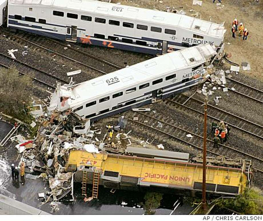 **FILE** This Jan. 2005 file photo shows Investigators as they examine the wreckage from a train derailment  in Glendale, Calif. A jury convicted a man of 11 counts of first-degree murder Thursday for causing the 2005 rail disaster that turned two commuter trains into a tangled mass of smoking wreckage littered with victims. Defendant Juan Alvarez, 29, who claimed he had only been trying to commit suicide when he started the deadly chain of events, looked on stolidly as the Superior Court jury returned verdicts that could lead to the death penalty. (AP Photo/Chris Carlson, file) Photo: CHRIS CARLSON, AP