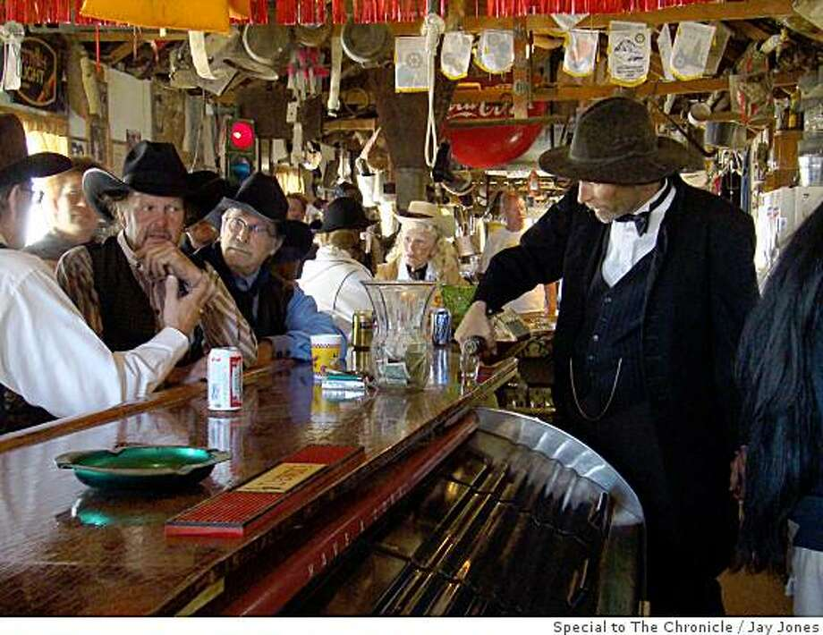 Volunteer Dan Adams serves up the drinks inside the saloon at Gold Point.  The bar is 110 feet long and the walls are covered with memorabilia from the town�s heyday. Photo: Jay Jones, Special To The Chronicle