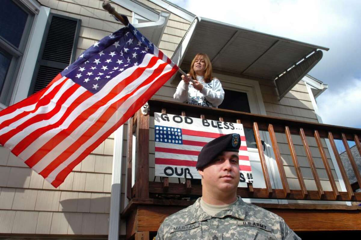 Staff Sgt. Nick Marsan of the Connecticut Army National Guard poses as his mother, Debbie, hangs a flag in front of the family home in Fairfield, Conn. on Nov. 6th, 2009. Marsan will deploy to Afghanistan with the 102nd Infintry later this month.