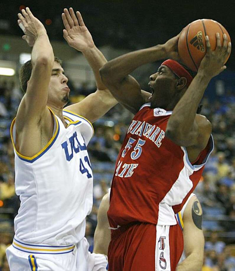 Delaware State's Frisco Sandidge, right, shoots over UCLA's Nikola Dragovic, of Serbia, during the first half of their NCAA college basketball game in Los Angeles on Sunday, Dec. 27, 2009. UCLA won 66-49. (AP Photo/Danny Moloshok) Photo: Danny Moloshok, AP
