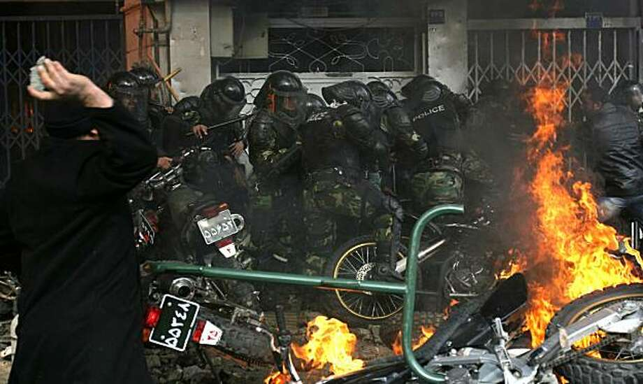 Police motorcycles burn as an Iranian opposition protester aims a stone at security forces during clashes in Tehran on December 27, 2009. Security forces shot dead four protesters in Tehran in a crackdown on vast crowds of opposition supporters who turned a Shiite mourning event into a mass protest, a website and witnesses said. AFP PHOTO/STR (Photo credit should read -/AFP/Getty Images) Photo: -, AFP/Getty Images